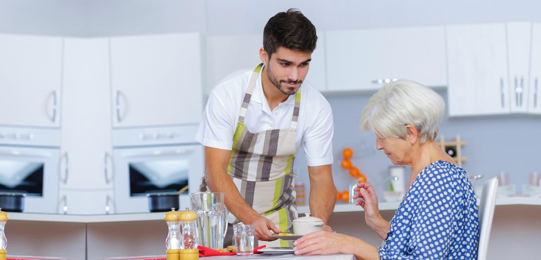 man preparing food for elderly woman