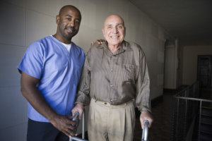 nurse and elderly man walking
